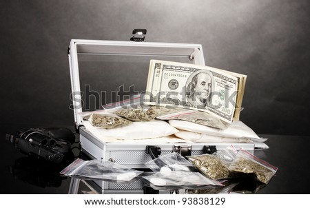 Cocaine and marijuana with gun in a suitcase on grey background - stock photo