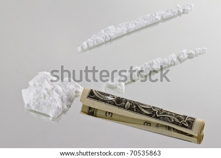 Cocaine cutted at mirror and ready to be sniffed trough a one dollar bill - stock photo