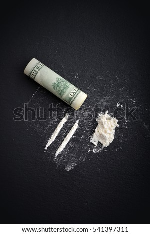 Cocaine drug addiction. Lines of cocaine and one hundred dollars banknote on black background  top view