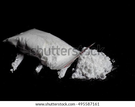 Cocaine drug powder in bag and cocaine powder pile and lines on black background
