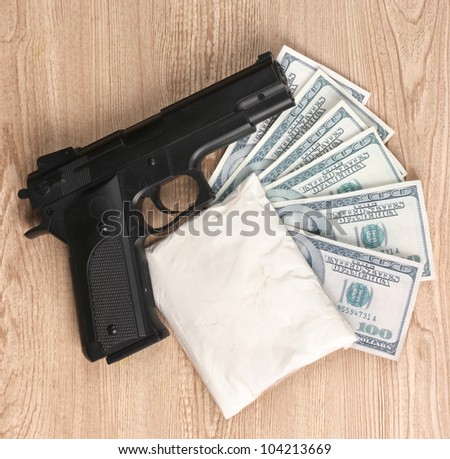 Cocaine in package, dollars and handgun on wooden background - stock photo