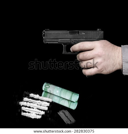 Cocaine powder in lines, money and razor blade with gun in the hand ready to shoot. Image done on the black background  - stock photo