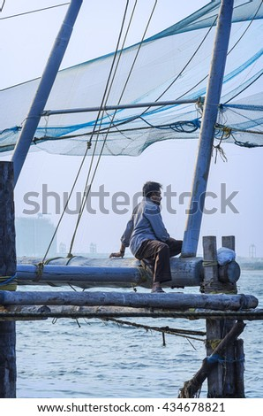COCHIN, INDIA - FEBRUARY 25, 2013: Lonely fisherman sitting on a wooden fishing platform port Cochin, South India. - stock photo