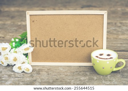 Cockboard with coffee and flower on wooden table in vintage tone - stock photo