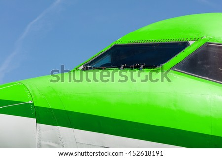 Cockpit close up of green jet airplane - stock photo