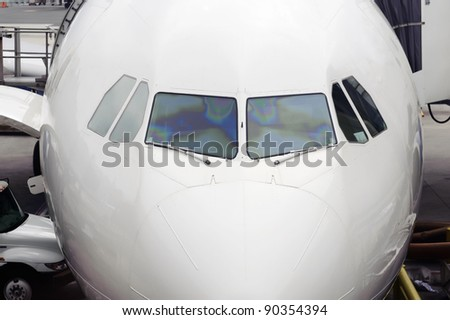 Cockpit close up of white jet airplane - stock photo
