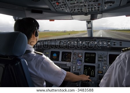 Cockpit crew starting takeoff roll - stock photo