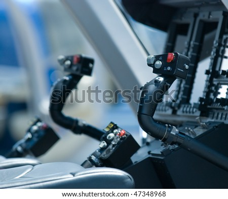 Cockpit of helicopter. Shallow depth of field with only the nearest control stick in focus. - stock photo