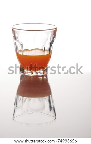 cocktai in the small glass with mirror reflection as white isolate background