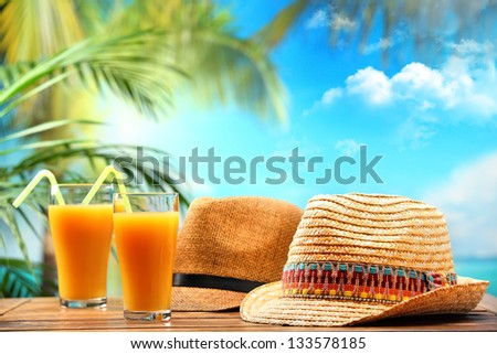 Cocktail and straw hat on beach table - stock photo