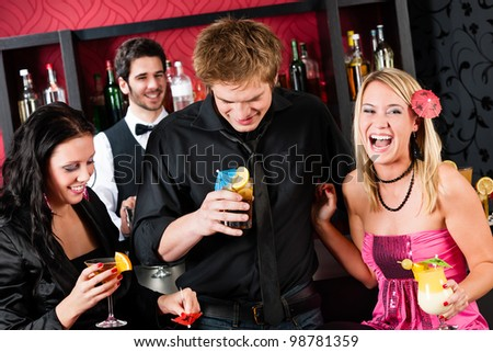 Cocktail bar laughing friends having fun at party time - stock photo