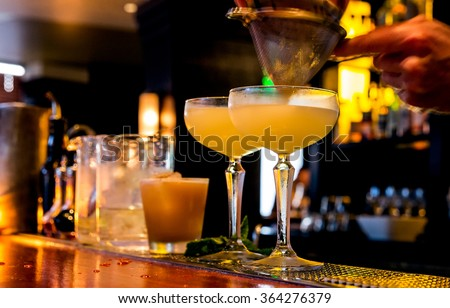 Cocktail being poured at a bar. Motion blur of the bartender's hand and strainer. Selective focus on the foreground glass. - stock photo