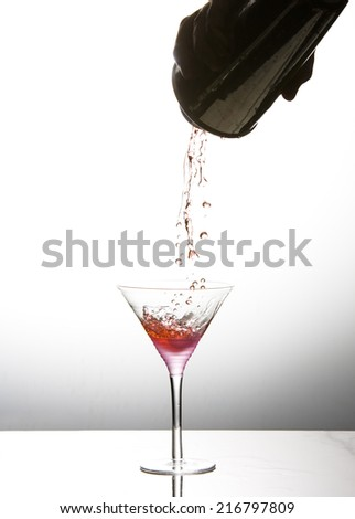 Cocktail being poured into martini glass
