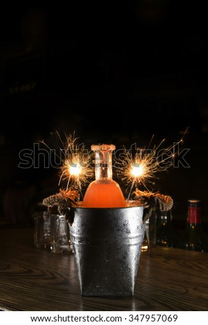 Cocktail bottle in tin can with firework sparkler for party - stock photo