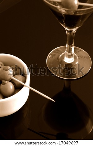 Cocktail & bowl of Olives close-up over reflective background - stock photo