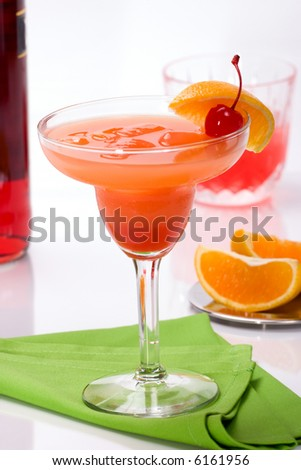 Cocktail campari with orange juice with slices of orange and campari in rocks out of focus in background. shallow dof. - stock photo