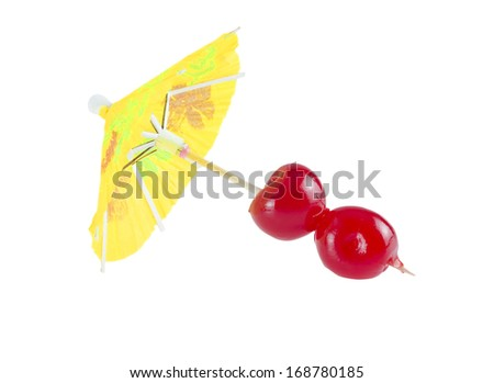 Cocktail cherry on party parasol isolated on white background. - stock photo