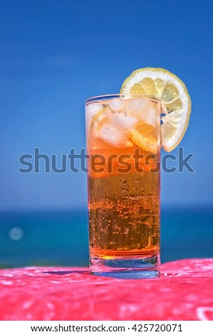 Cocktail drink in front of summer sea and sky background - stock photo