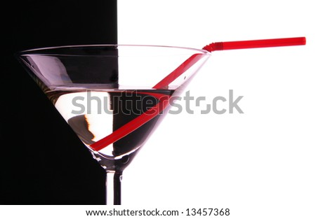 Cocktail glass close-up with red sraw over black and white background - stock photo