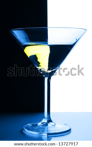Cocktail glass close-up with red sraw over contrast black and white background - stock photo