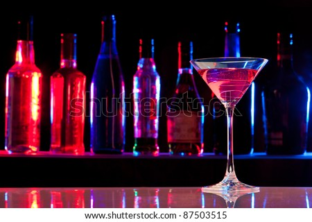 Cocktail glass with drink in the bar with bottles in the dark background - stock photo