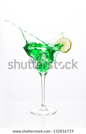 Cocktail glass with green alcohol and lemon on white background