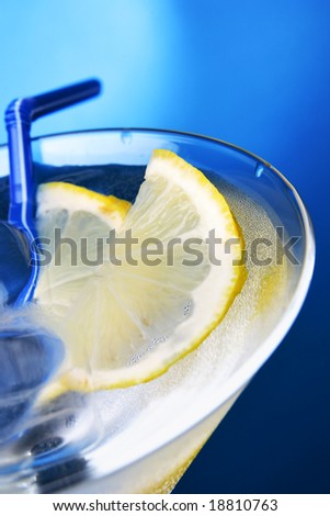 Cocktail glass with ice cubes and lemon slice - stock photo