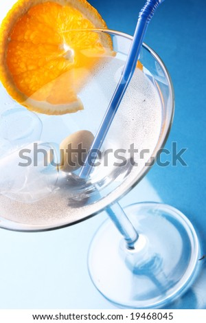 Cocktail glass with orange slice over blue background - stock photo