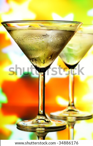 Cocktail glasses with ice and holiday lights in the background - stock photo