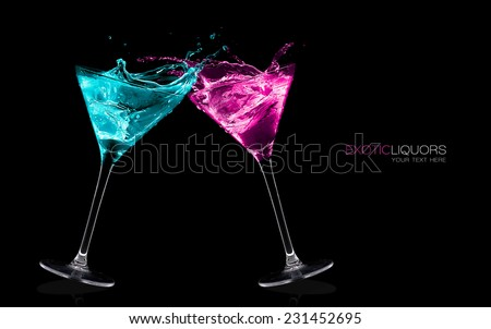 Cocktail glasses with long stems full of colorful liquors making a toast splashing out, close-up isolated on black, with sample text. Party concept. Colorful splashes. Template design - stock photo