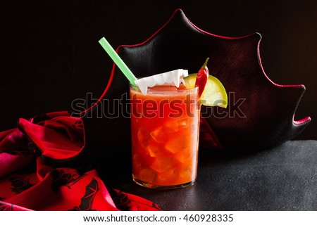 "Cocktail Halloween ""Vampiro"" of tomato juice with tequila and ice in a glass on a black background, horizontal"