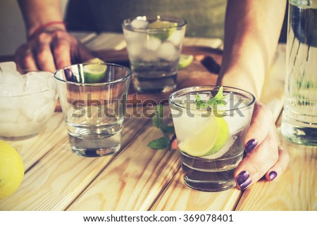 cocktail in a glass with ice. Vodka, tequila, gin. A young girl, the woman proposes Mojitos, non-alcoholic, refreshing drink,  vodka, tequila, gin into a glass with ice, lime and mint.  - stock photo