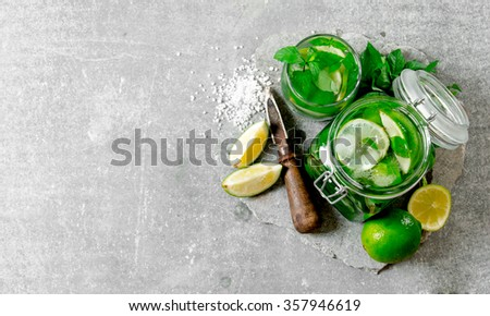Cocktail in jar - mint leaves, ice, rum and lime on a stone base with a knife for citrus and sugar . Free space for text . Top view - stock photo