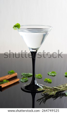 Cocktail in martini glass on the black glass table - stock photo