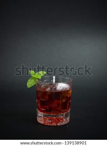 Cocktail made with gin and red liquor, decorated with mint leaves, isolated on dark background. - stock photo