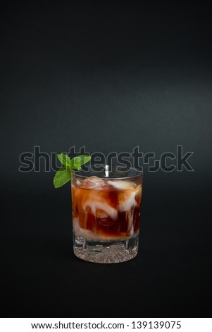 Cocktail made with vodka, red liquor and drops of yogurt liquor, decorated with mint leaves, isolated on dark background. - stock photo
