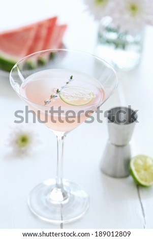 Cocktail mocktail drink in a martini glass decorated with a slice of lime on a white table  - stock photo