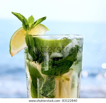 Cocktail mojito ice lemon on the background of the ocean - stock photo