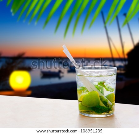 Cocktail Mojito in Balearic island sunset and palm trees [photo-illustration] - stock photo