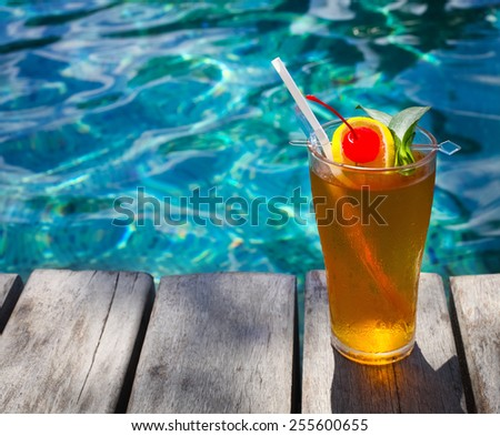 Cocktail near the swimming pool on the background of the water - stock photo