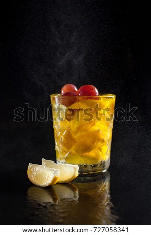 cocktail of lemon in a glass on a black background with lemon slices and splashing drops with reflection, on a black background