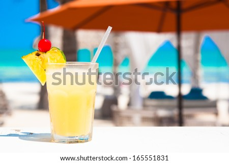 cocktail on wooden planks in front of a blue  ocean - stock photo