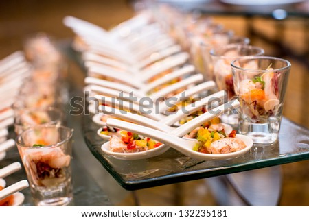 Cocktail party with variety of desserts and food decorated in spoons arranged in orderly fashion - stock photo
