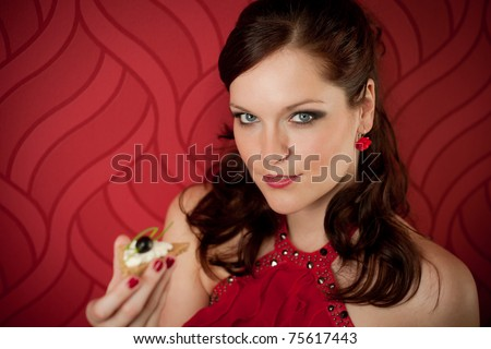 Cocktail party woman eat appetizer evening dress red background - stock photo