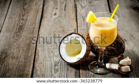 Cocktail Pina colada. A fresh cocktail in a glass with coconut on wooden table. Free space for text. - stock photo