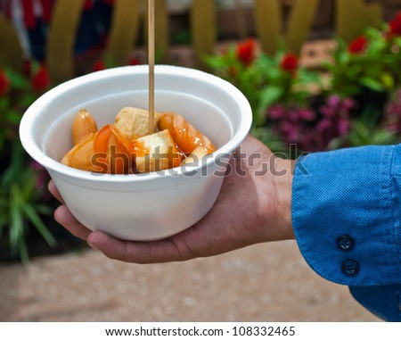 Cocktail sausages in men hand with blue shirt. - stock photo