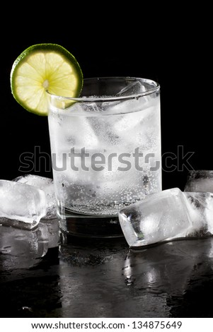 cocktail served on a dark bar top garnished with a lime wheel - stock photo