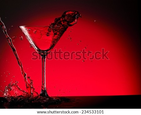 Cocktail splash with drops on red background - stock photo