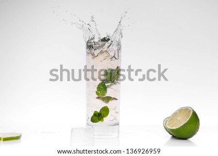 cocktail splashing into glass and cube of ice