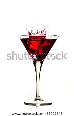 cocktail splashing into glass on white background